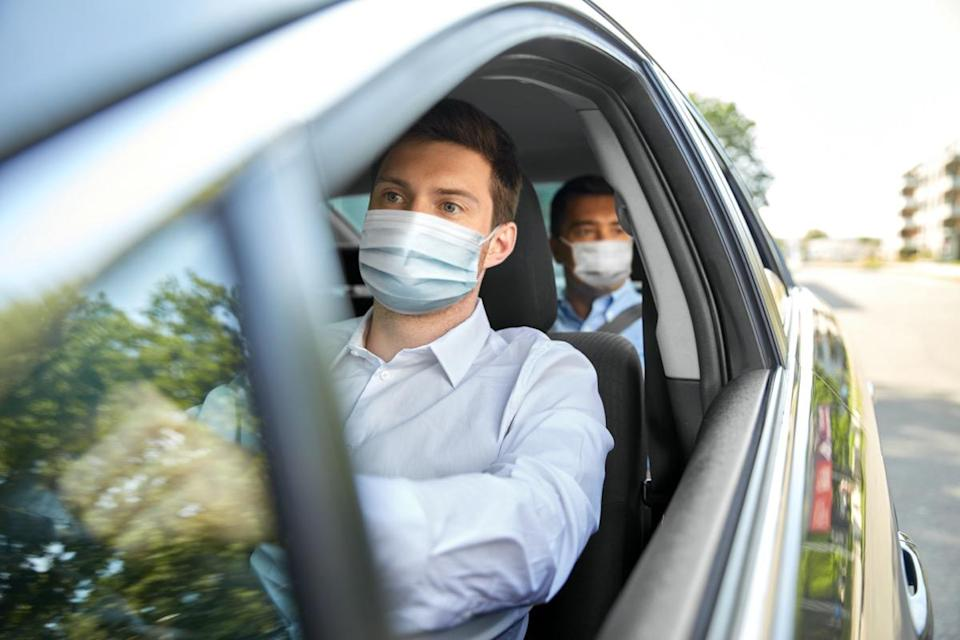 male taxi driver wearing face protective medical mask driving car with passenger