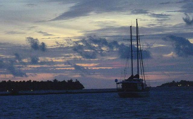 A two-masted yacht drops anchor at sunset in the high sea off a resort island. A variety of water-craft can be seen in the Maldives, which relies heavily on them for transportation between islands.