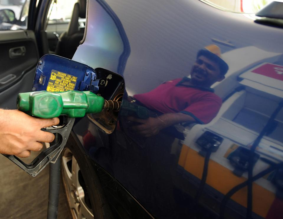 A pump attendant fills up a vehicle with fuel at a petrol kiosk in Singapore. (PHOTO: Roslan Rahman/AFP via Getty Images)