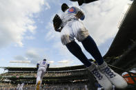 Chicago Cubs' Jason Heyward right, jumps on the field from the dugout while Javier Baez (9) and other teammates run on the field before a baseball game against the Cleveland Indians Tuesday, June 22, 2021, at Wrigley Field in Chicago. (AP Photo/Paul Beaty)
