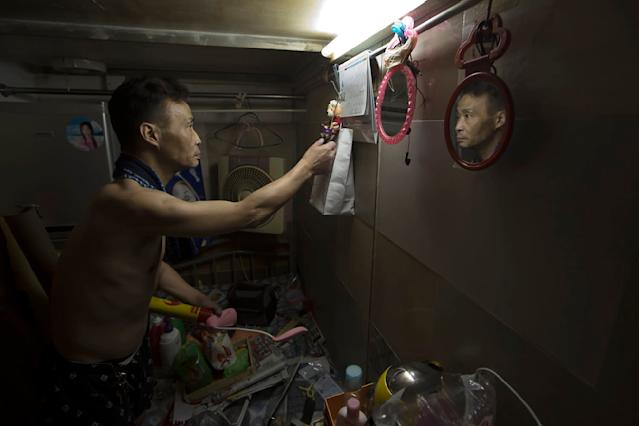 "<p>A resident who only gave his surname Sin, 55, tidies up the bed in his ""coffin home"" in Hong Kong. (Photo: Kin Cheung/AP) </p>"