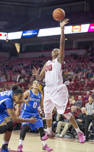 Arkansas forward Jessica Jackson, right, shoots after driving past Kentucky defenders Jelleah Sidney, left, and Jennifer O'Neill, center, during the first half of an NCAA college basketball game Thursday, Feb. 26, 2015, in Fayetteville, Ark. Kentucky defeated Arkansas 56-51. (AP Photo/Gareth Patterson)
