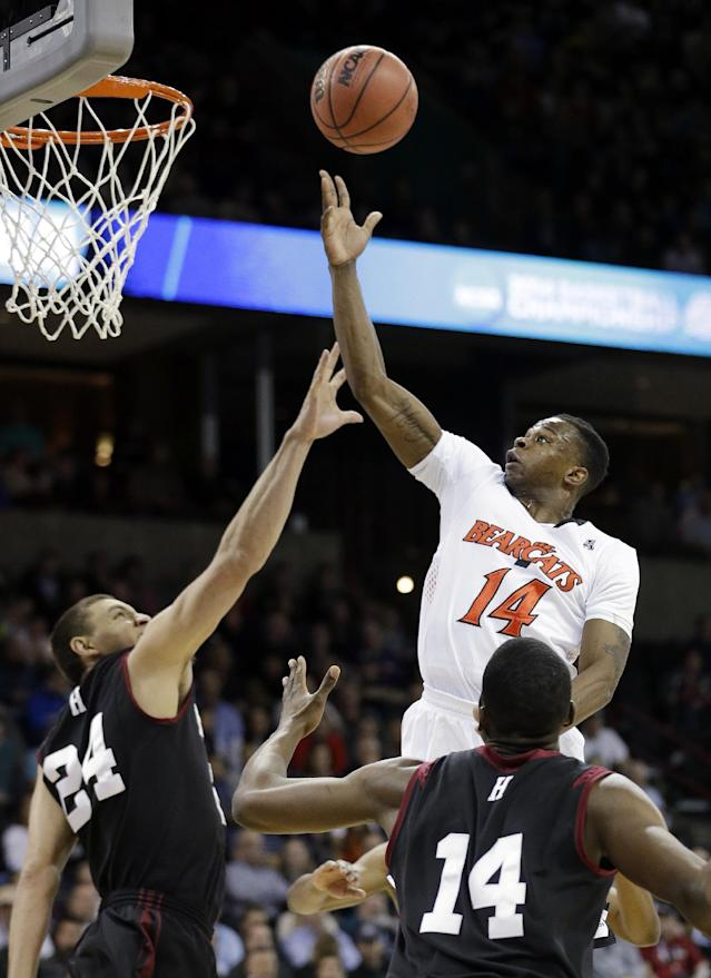 Cincinnati's Ge'Lawn Guyn (14) puts up a shot over Harvard's Jonah Travis (24) and Steve Moundou-Missi during the first half of a second-round game of the NCAA college basketball tournament in Spokane, Wash., Thursday, March 20, 2014. (AP Photo/Elaine Thompson)