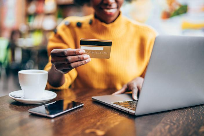 Cropped shot of young african-american woman shopping online in cafe using laptop and credit card.