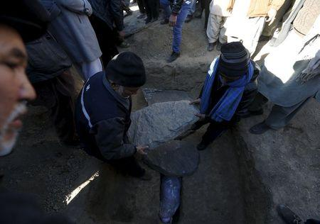 Afghans take part in a burial ceremony for one of the victims of last night suicide car bomb attack in Kabul, Afghanistan