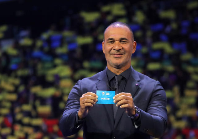 Netherland's former soccer player Ruud Gullit holds up the name Poland during the draw for the UEFA Euro 2020 soccer tournament finals in Bucharest, Romania, Saturday, Nov. 30, 2019. (AP Photo/Vadim Ghirda)
