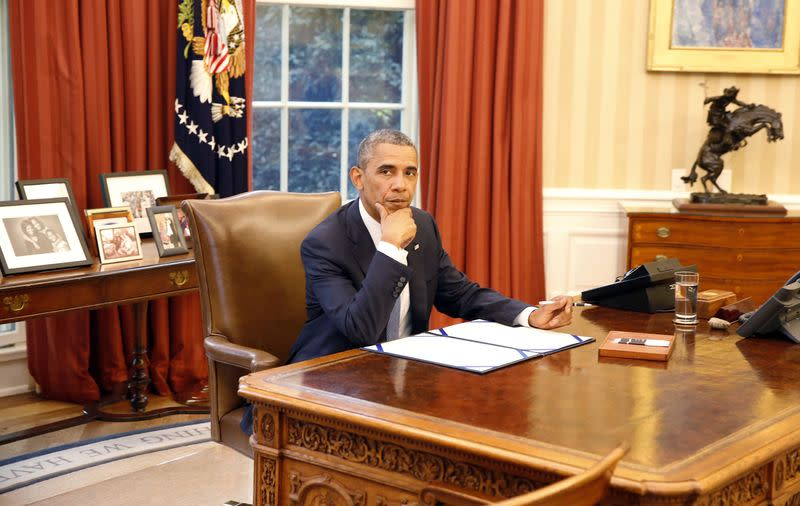 U.S. President Barack Obama reacts before he signs into law S. 517, Unlocking Consumer Choice and Wireless Competition Act, in the Oval Office at the White House in Washington,