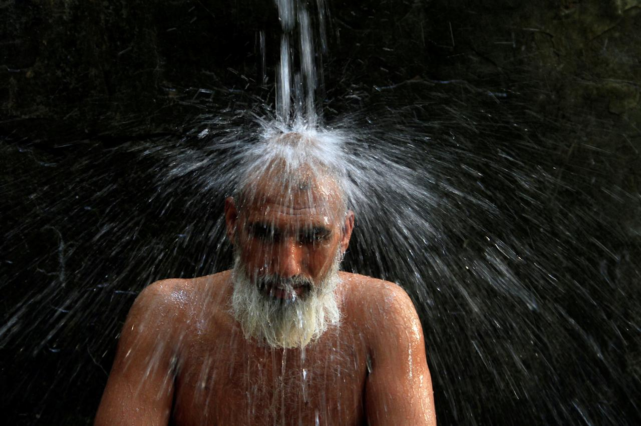 A man cools off from the heatwave, as he takes a shower at a public bath in Lahore, Pakistan May 27, 2018. REUTERS/Mohsin Raza