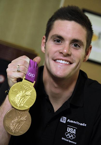 David Boudia, who came back from the 2012 London Summer Olympics having won both gold and bronze in diving, shows off his medals during an interview, Monday, Aug. 13, 2012, in New York. (AP Photo/Richard Drew)