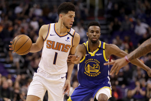Phoenix Suns guard Devin Booker (1) looks to pass as Golden State Warriors guard Andrew Wiggins (22) defends during the second half of an NBA basketball game, Wednesday, Feb. 12, 2020, in Phoenix. (AP Photo/Matt York)