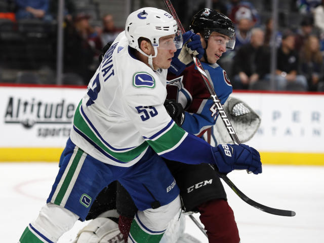 Vancouver Canucks center Bo Horvat, left, fights for position by the net with Colorado Avalanche defenseman Samuel Girard in the second period of an NHL hockey game Monday, Feb. 26, 2018, in Denver. (AP Photo/David Zalubowski)
