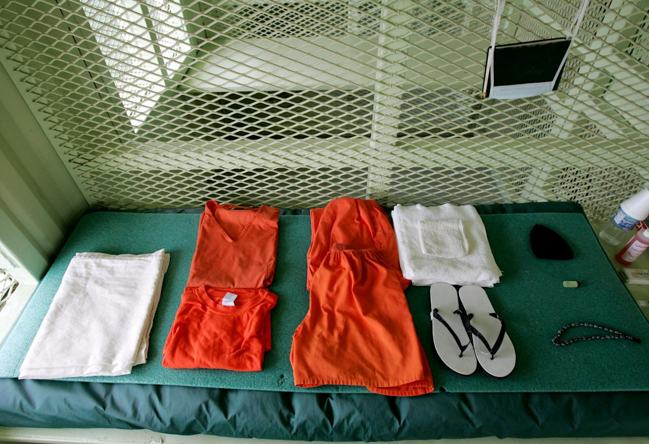 GUANTANAMO BAY, CUBA - AUGUST 23:  A uniform and other supplies that are given to detainees lie on a bed in a cell at Camp Delta at Guantanamo Naval Base August 23, 2004 in Guantanamo, Cuba. On August 24, preliminary hearings will begin for four suspected Al Qaeda associates charged by the U.S. with war crimes as they appear before a commission of five military officers.  (Photo by Mark Wilson/Getty Images)