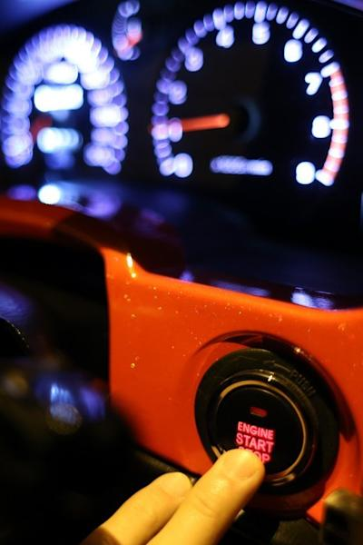 To go with Lifestyle-Asia-HongKong-crime-auto,FEATURE by Preeti Jha In a picture taken on April 7, a driver pushes the engine start button on his modified racing car before a race in the early hours of the morning in Hong Kong. As night begins to give way to dawn, 40 high-performance cars pull up on an empty Hong Kong backstreet. Their revving engines fill the air with a heavy smell of petrol as the city sleeps. AFP PHOTO / AARON TAM