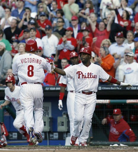 Philadelphia Phillies' Shane Victorino (8) celebrates with teammate Jimmy Rollins after they scored against the Boston Red Sox on a single hit by Carlos Ruiz in the first inning of a baseball game on Friday, May 18, 2012, in Philadelphia. (AP Photo/H. Rumph Jr)