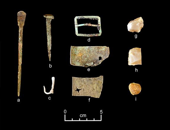 Artifacts discovered from the Neva shipwreck include (from left) part of a set of dividers, a nail, a fishhook, a buckle, sheet copper, gun flints and a musket ball.