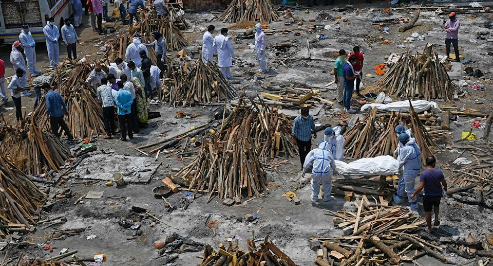 TOPSHOT - Family members and relatives prepare the funeral pyre of victims who died of the Covid-19 coronavirus during mass cremation held at a crematorium in New Delhi on April 27, 2021. (Photo by Prakash SINGH / AFP) (Photo by PRAKASH SINGH/AFP via Getty Images)