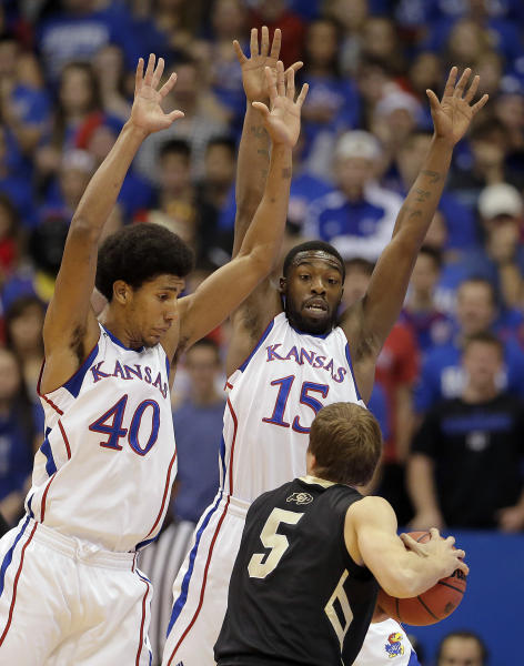 Colorado guard Eli Stalzer (5) is pressured by Kansas forward Kevin Young (40) and guard Elijah Johnson (15) during the first half of an NCAA college basketball game Saturday, Dec. 8, 2012, in Lawrence, Kan. (AP Photo/Charlie Riedel)