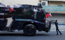 FILE PHOTO: A protester, holding a Bahraini flag, confronts a riot police armoured personnel carrier in an attempt to stop it from entering the village of Bilad Al Qadeem