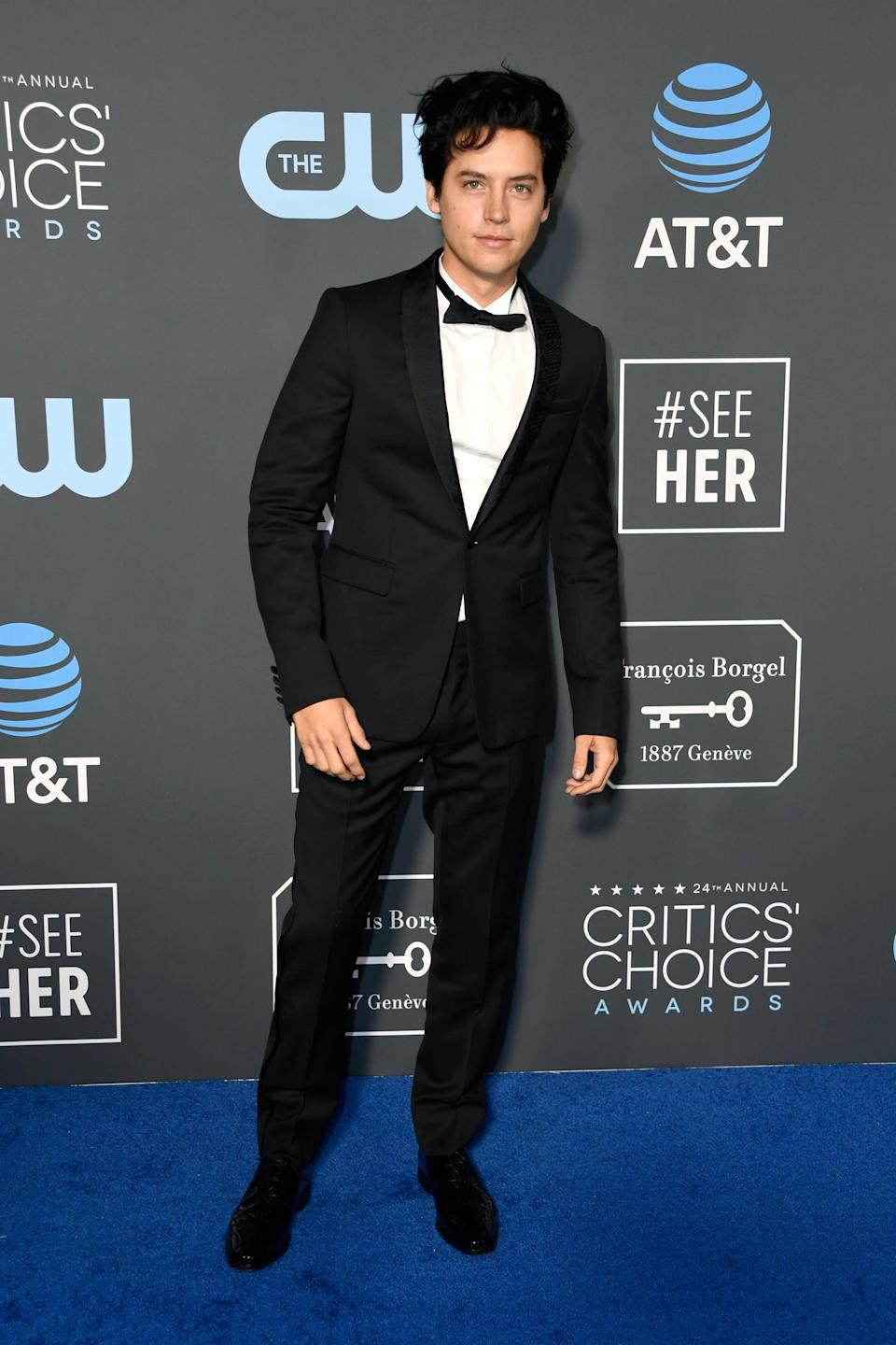 <p>Cole Sprouse wearing a black suit and bowtie.</p>