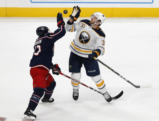 Columbus Blue Jackets forward Cam Atkinson, left, and Buffalo Sabres defenseman Colin Miller try to redirect the puck during the third period of an NHL hockey game in Columbus, Ohio, Monday, Oct. 7, 2019. (AP Photo/Paul Vernon)