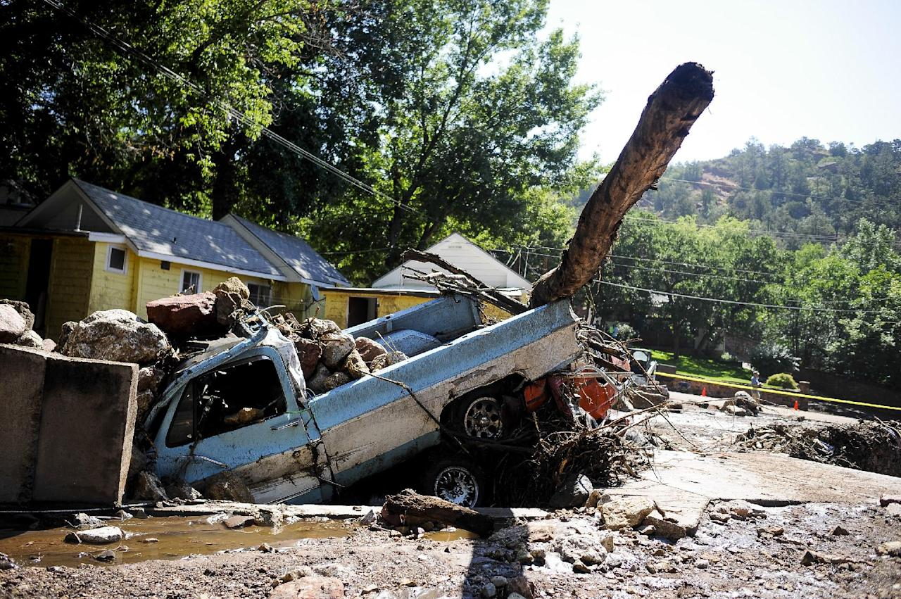 A truck and car is washed away by a flash flood that hit Manitou Springs, Colo., Friday sits in a drainage, covered in rocks, Saturday, Aug. 10, 2013. Friday's torrential rains swept mud, boulders and other debris from the burn scar down U.S. 24, washing away vehicles and damaging several homes and businesses in the area. (AP Photo/The Colorado Springs Gazette, Michael Ciaglo) MAGS OUT