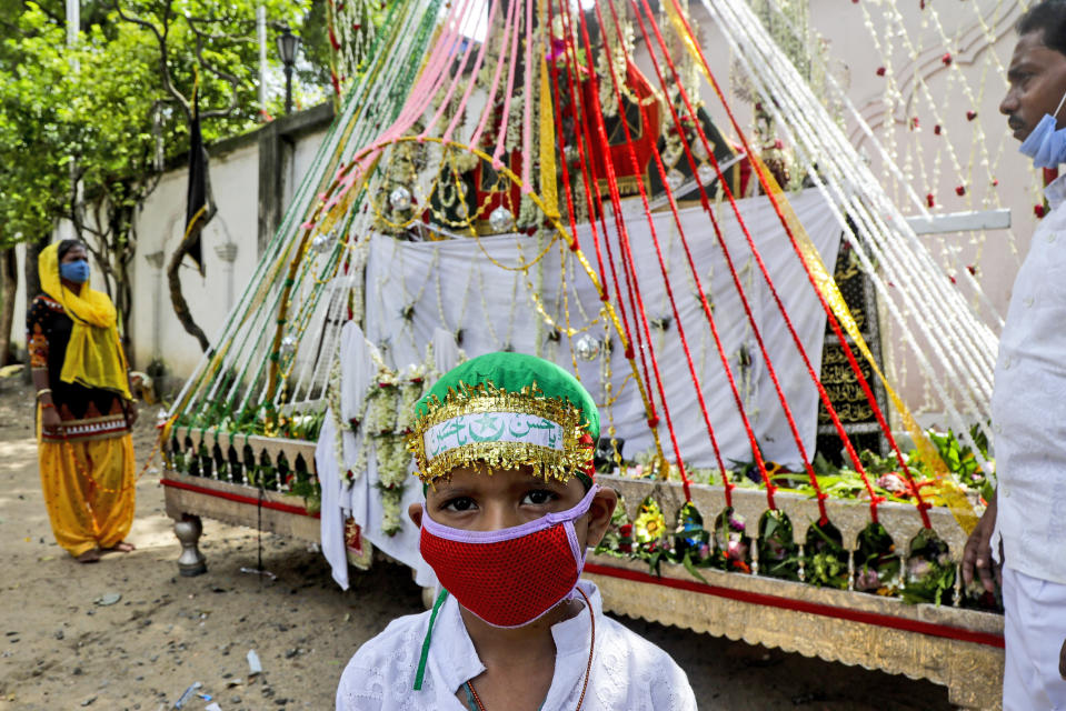A Muslim boy wearing face mask stands in front of a replica of the highest seat of Imam Hussain, the great grandson of Prophet Muhammad prior to a Muharram procession in Kolkata, India, Sunday, Aug. 30, 2020. India has the third-highest coronavirus caseload after the United States and Brazil, and the fourth-highest death toll in the world. (AP Photo/Bikas Das)