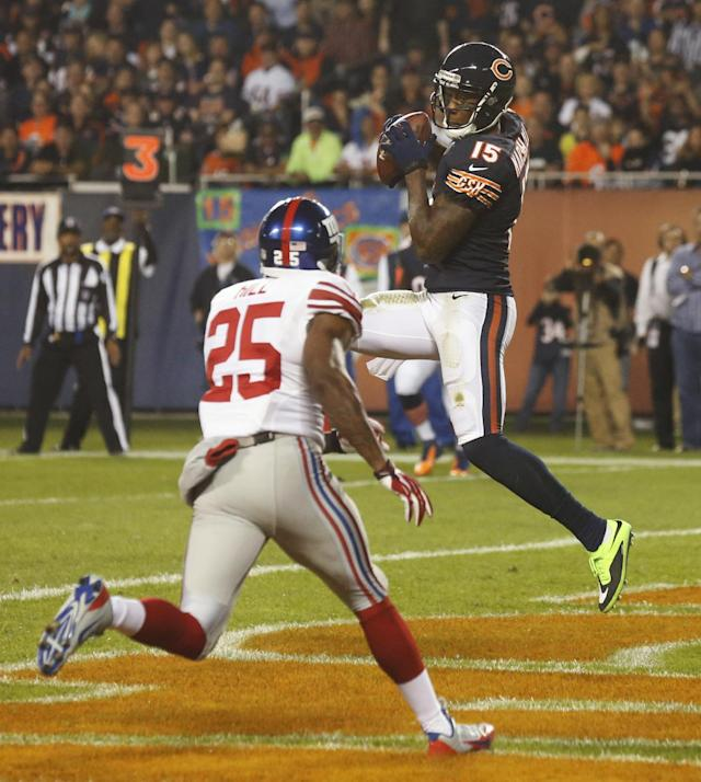 Chicago Bears wide receiver Brandon Marshall (15) makes a touchdown reception in front of New York Giants defensive back Will Hill (25) in the first half of an NFL football game, Thursday, Oct. 10, 2013, in Chicago. (AP Photo/Charles Rex Arbogast)