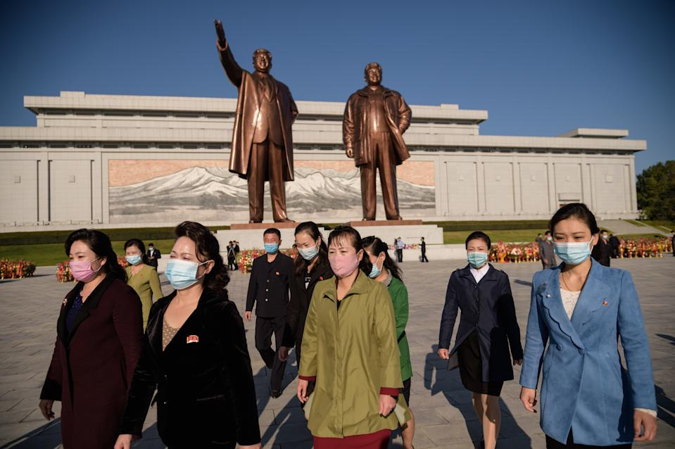 People leave after paying their respects before the statues of late North Korean leaders Kim Il Sung and Kim Jong Il at Mansu hill, as the country marks the 75th founding anniversary of the Workers' Party of Korea, in Pyongyang on October 10, 2020. (Photo by KIM Won Jin / AFP) / The erroneous mention[s] appearing in the metadata of this photo by Kim Won Jin has been modified in AFP systems in the following manner: [Kim Won Jin] instead of [Ed Jones]. Please immediately remove the erroneous mention[s] from all your online services and delete it (them) from your servers. If you have been authorized by AFP to distribute it (them) to third parties, please ensure that the same actions are carried out by them. Failure to promptly comply with these instructions will entail liability on your part for any continued or post notification usage. Therefore we thank you very much for all your attention and prompt action. We are sorry for the inconvenience this notification may cause and remain at your disposal for any further information you may require. (Photo by KIM WON JIN/AFP via Getty Images)