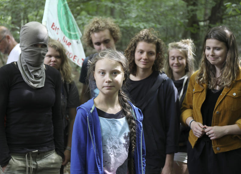 Climate activist Greta Thunberg, center, stands together with environmentalist protesters as she visits the ancient Hambach Forest near the city of Kerpen in western Germany, Aug. 10, 2019. The teenage activist who is a leading figure in the Fridays for Future strikes against climate said that seeing the open-cast lignite pit in Hambach disturbed her deeply and that the time has come to stop talking and take action. Right are Luisa Neubauer a leading face of Germany's Friday for Future movement. (Oliver Berg/dpa via AP)