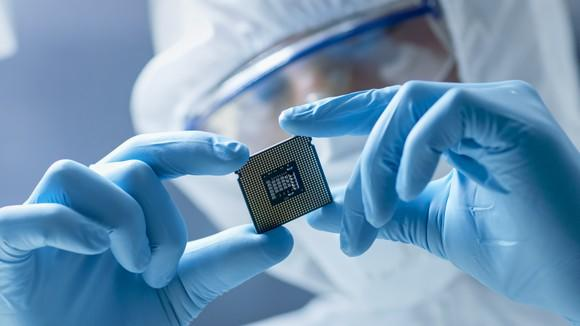Worker in a clean room suit examining a chip