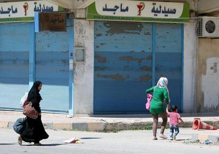 Women carry their belongings as they flee clashes in the southeast of Qamishli city