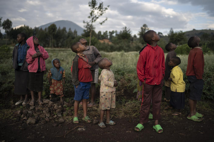 Children watch a drone flying near Volcanoes National Park in Kinigi, Rwanda. In 2005, the government adopted a model to steer 5 percent of tourism revenue from Volcanoes National Park to build infrastructure in surrounding villages, including schools and health clinics. Two years ago, the share was raised to 10 percent. (Photo: Felipe Dana/AP)