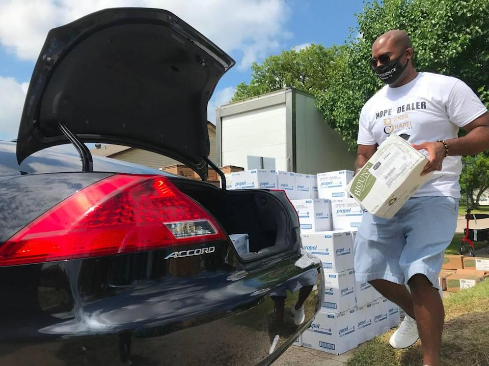 The Rev. Melvin Wilson Jr. of Baker Chapel AME in Fort Worth, TX loads a box of food into a car on Saturday. He said the church has been giving out free food and water, in partnership with Community Food Bank, since the historic winter storms passed in February.