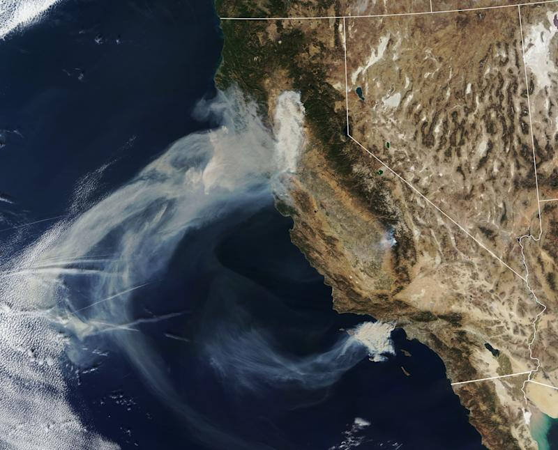 Massive plumes of smoke billow Friday over the state. (NASA)