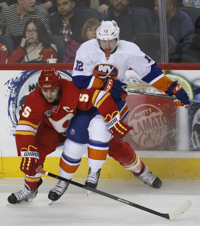 New York Islanders' Josh Bailey (12) battles Calgary Flames' Mark Giordano during the third period of an NHL hockey game Friday, March 7, 2014, in Calgary, Alberta. (AP Photo/The Canadian Press, Jeff McIntosh)