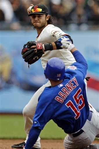 San Francisco Giants shortstop Brandon Crawford attempts a double play over Chicago Cubs' Darwin Barney (15) after a bunt from Jeff Samardzija during the fourth inning of a baseball game in San Francisco, Monday, June 4, 2012. Samardzija was safe at first base. (AP Photo/Marcio Jose Sanchez)