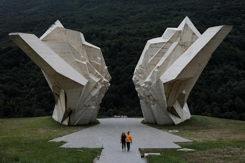 """A couple walk in front of the war memorial monument """"Battle of Sutjeska"""" in Tjentiste, Bosnia and Herzegovina. Examples of Yugoslav brutalism include the huge memorials commemorating the struggle against fascism, often placed in dramatic rural settings. Many of those pieces of art remain in disrepair; however, the Tjentiste memorial, commemorating the killing of 7,000 people by the Nazis was renovated last year. (Photo: Marko Djurica/Reuters)"""