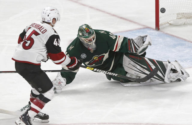 Arizona Coyotes' Josh Archibald, left, scores his second of two third-period goals off Minnesota Wild goalie Devan Dubnyk, right, during an NHL hockey game Tuesday, Nov. 27, 2018, in St. Paul, Minn. The Coyotes won 4-3. (AP Photo/Jim Mone)