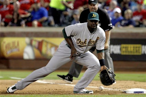 Oakland Athletics first baseman Chris Carter is unable to field a ball off the bat of Texas Rangers' Mitch Moreland in the fourth inning of a baseball game, Monday, Sept. 24, 2012, in Arlington, Texas. Moreland advanced to second on the error by Carter. (AP Photo/Tony Gutierrez)