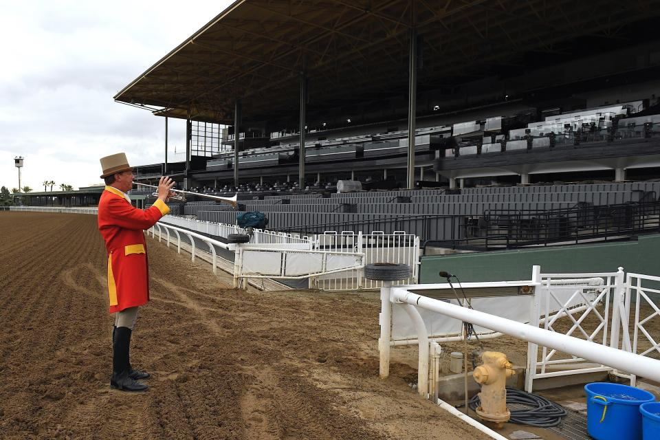 Bugler Jay Cohen trumpets the first race at Santa Anita Park to empty stands Saturday, March 14, 2020, in Arcadia, Calif. (AP Photo/Mark J. Terrill)
