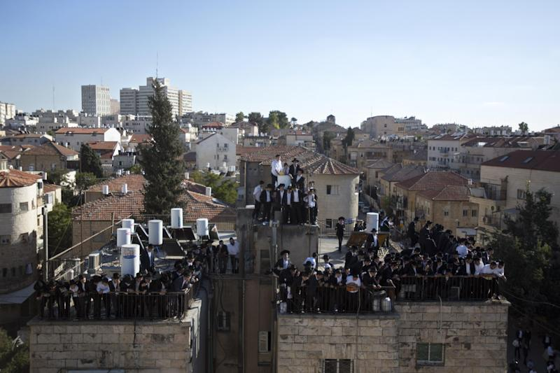 Orthodox Jews gather on a rooftop to watch the funeral procession of Rabbi Ovadia Yosef in Jerusalem, Monday, Oct. 7, 2013. Rabbi Yosef, 93, a religious scholar and spiritual leader of Israel's Sephardic Jews, transformed his downtrodden community of immigrants from North Africa and Arab nations and their descendants into a powerful force in Israeli politics. (AP Photo/Sebastian Scheiner)