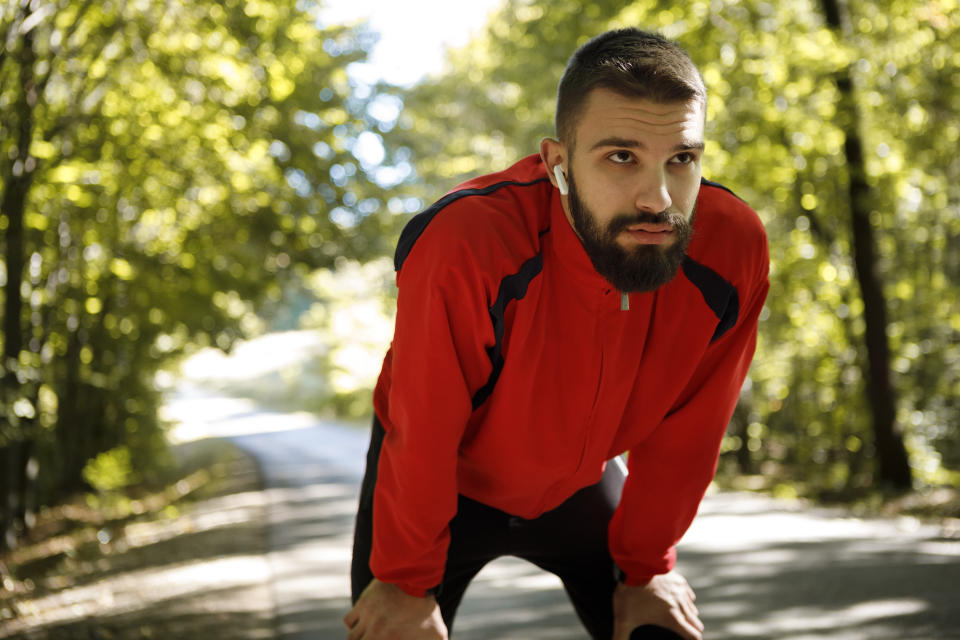 Portrait of young handsome man with bluetooth headphones resting while jogging in forest