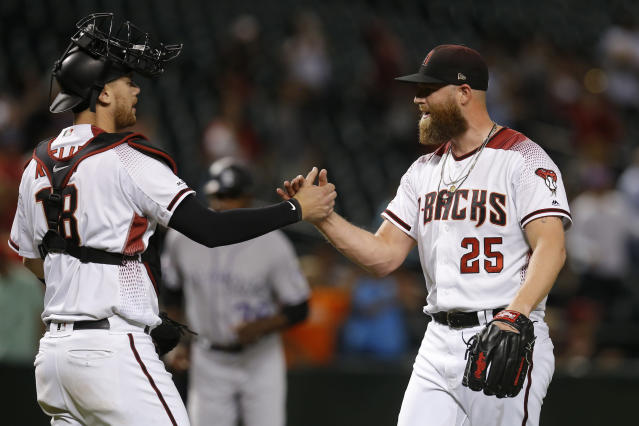 Arizona Diamondbacks catcher Carson Kelly and pitcher Archie Bradley (25) celebrate after the team defeated the Colorado Rockies 5-3 in a baseball game, Monday, Aug. 19, 2019, in Phoenix. (AP Photo/Rick Scuteri)