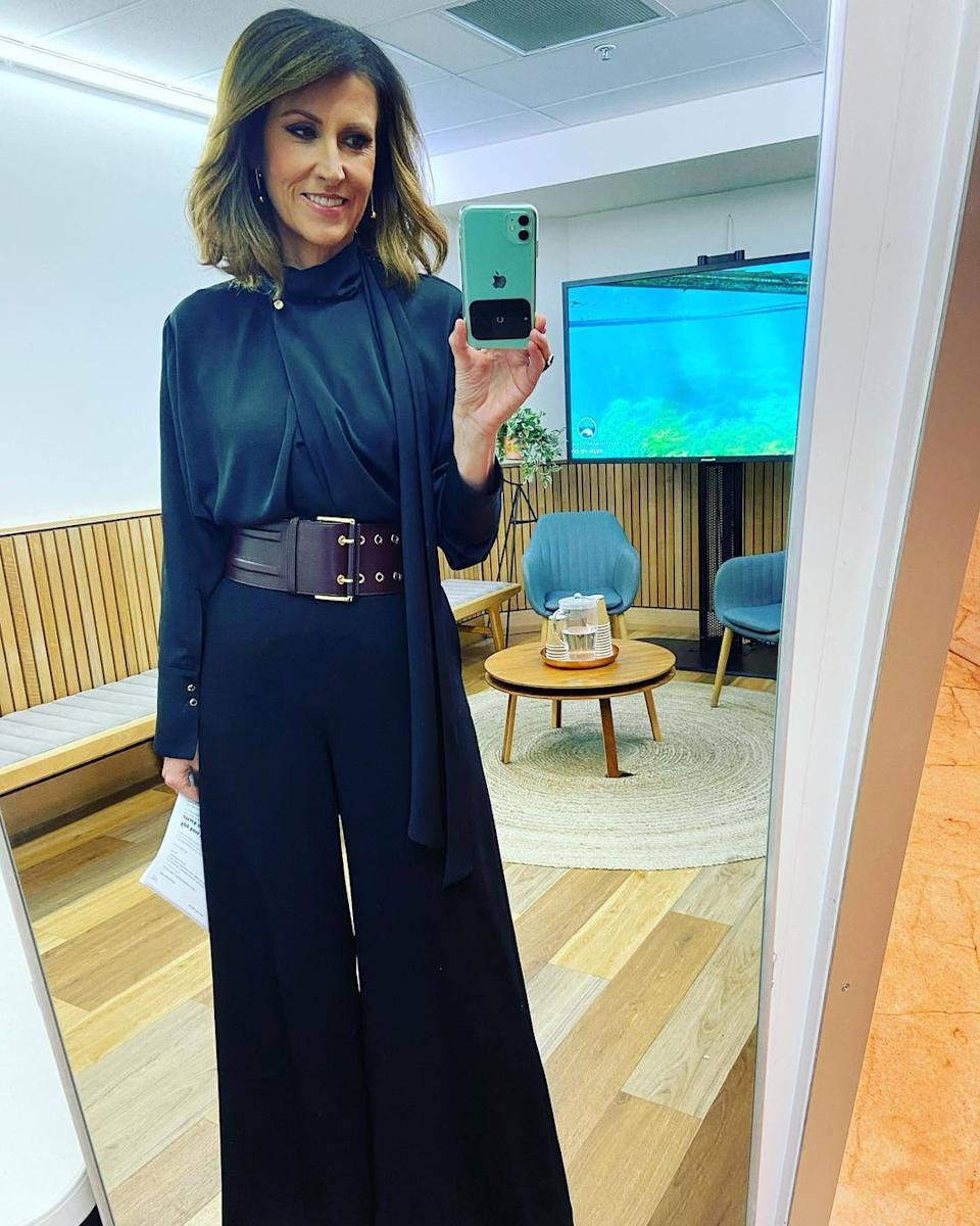 Sunrise host Nat Barr poses for a selfie in front of a large mirror while wearing black pants, a black blouse and a maroon wide belt