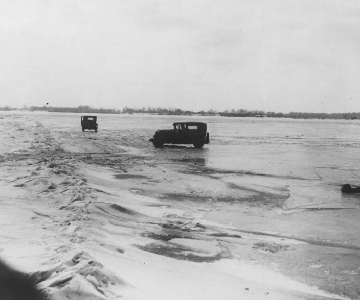 FILE - In this Feb. 14, 1930, file photo large quantities of Canadian beer and whisky are being transported in cars from Amherstburg, Ont., Canada, across the frozen lower Detroit River, to the Michigan side of the international boundary line. The cars are driven with one door open, so if the car goes through the ice the driver can scramble free. (AP Photo, File)