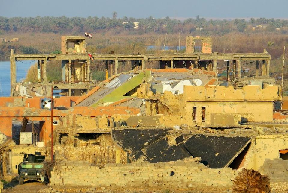 Iraqi flags fly above destroyed buildings in the rural Husayba al-Sharkiya area, east of Ramadi on December 20, 2015 (AFP Photo/STR)