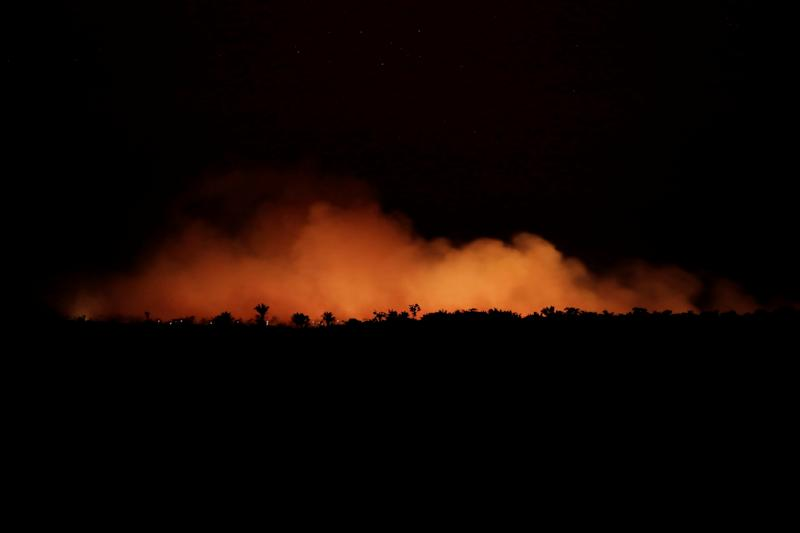 Orange smoke is seen at night during a fire in an area of the Amazon forest. Source: Reuters