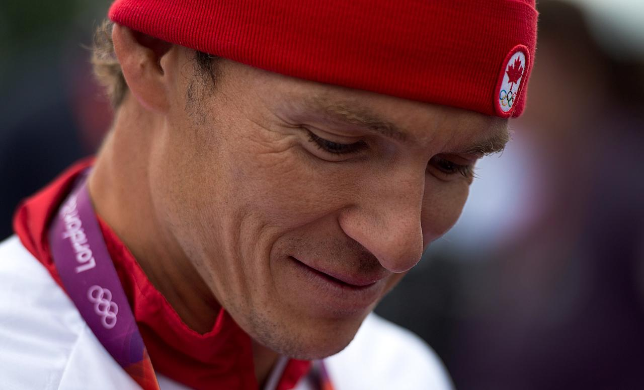 Canada's Simon Whitfield talks to reporters after crashing and retreating from the men's triathlon at Hyde Park during the Summer Olympics in London on Tuesday, August 7, 2012. THE CANADIAN PRESS/Sean Kilpatrick