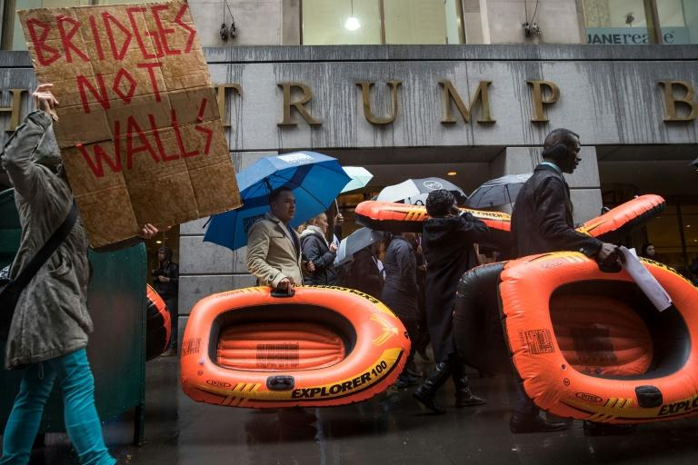People carry rafts, signifying the struggle of refugees, as they march on Wall Street during a protest against the Trump administration's proposed travel ban and refugee policies, in New York, on March 28, 2017