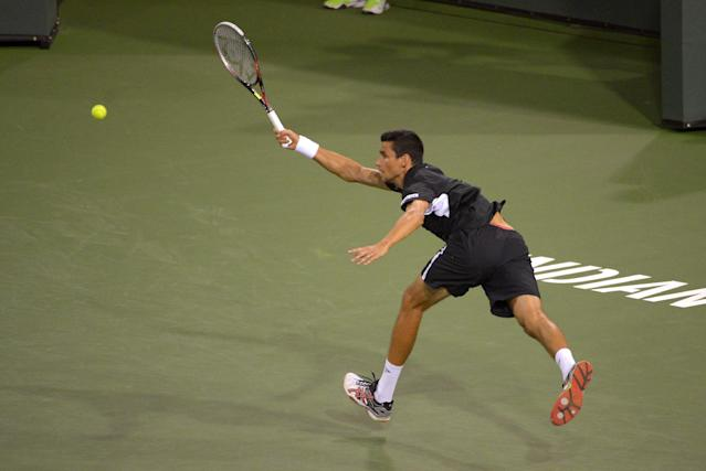 Victor Hanescu, of Romania, returns a shot to Novak Djokovic, of Serbia, during their match at the BNP Paribas Open tennis tournament, Sunday, March 9, 2014, in Indian Wells, Calif. (AP Photo/Mark J. Terrill)